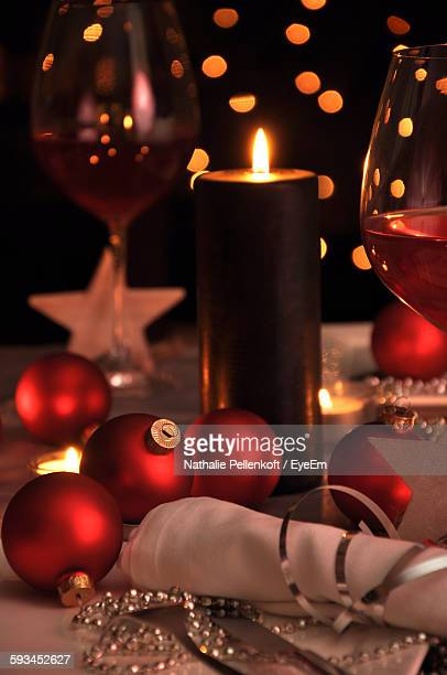 illuminated candle amidst christmas decorations and wine on table - nathalie pellenkoft stock pictures, royalty-free photos & images