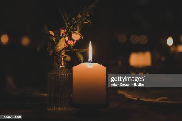 illuminated candle on table in darkroom - burns night stock pictures, royalty-free photos & images