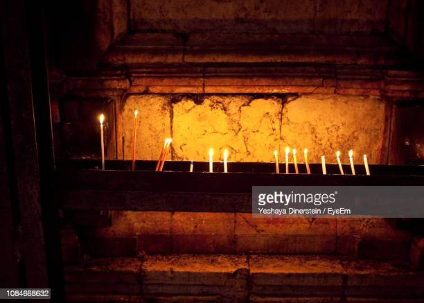 Illuminated Candles Against Wall