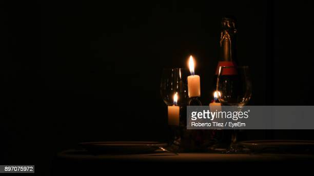 Illuminated Candles And Wineglasses Against Black Background