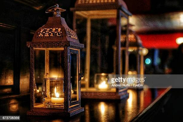 illuminated candles in containers on table - andres ruffo stock-fotos und bilder