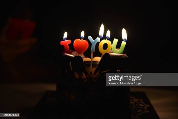 illuminated candles on cake in dark - love you stock photos and pictures