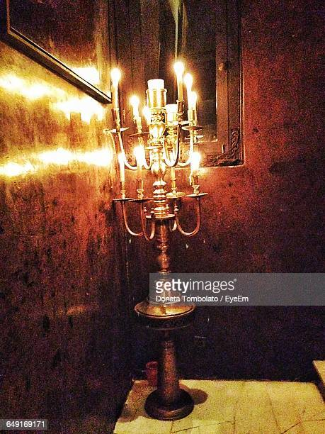 Illuminated Candles On Holder By Wall At Home