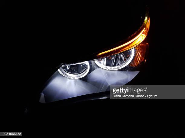 illuminated car headlight at night - headlight stock pictures, royalty-free photos & images