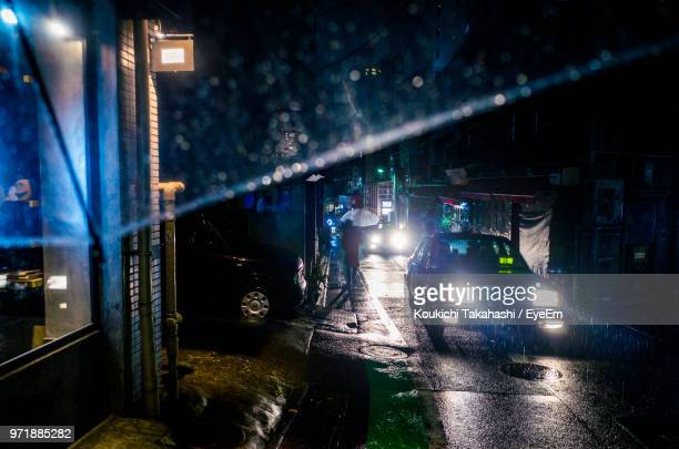Illuminated Car Headlight On Street During Rainfall At Night