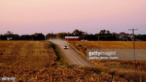 illuminated car moving on road amidst agricultural field against sky during sunset - nebraska stock pictures, royalty-free photos & images