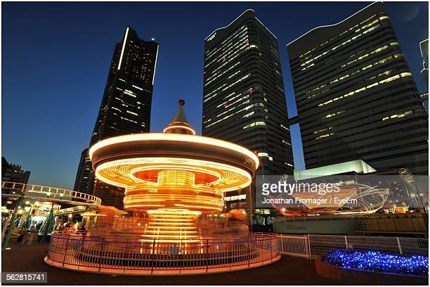 Illuminated Carousel Against Skyscrapers At Night