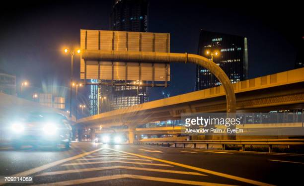 Illuminated Cars Moving On Road By Overpass In City At Night