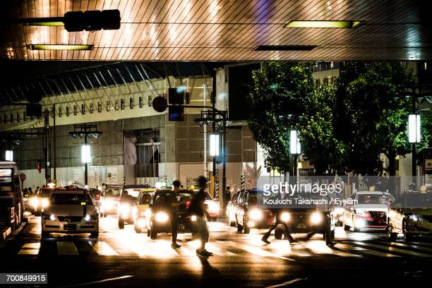 Illuminated Cars Moving On Road In City At Night