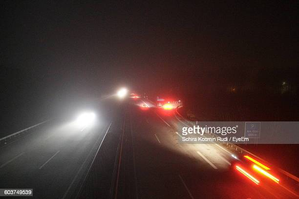 Illuminated Cars On Highway Against Sky At Night