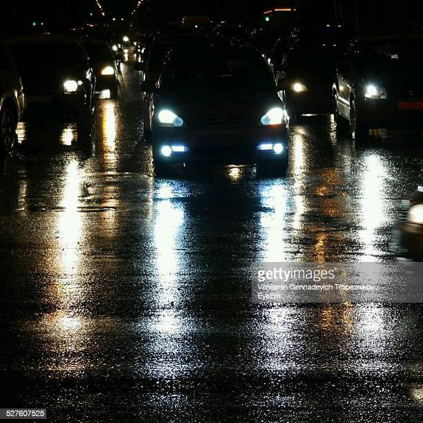 Illuminated Cars On Wet Street At Night