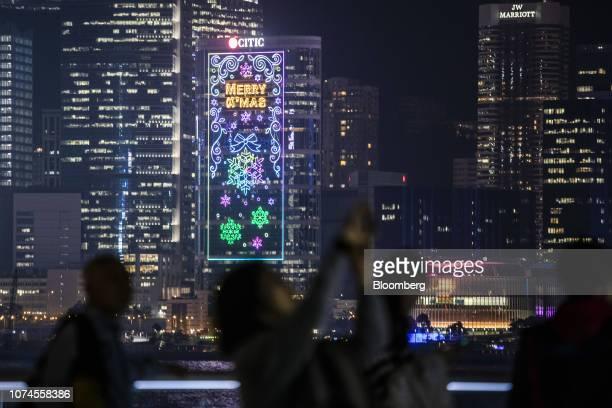 Illuminated Christmas lights decorate the exterior of Citic Tower at night in Hong Kong, China, on Thursday, Dec. 20, 2018. Hong Kong's consumer...