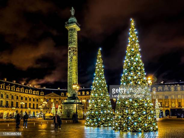 illuminated christmas tree against building at night - paris france stock pictures, royalty-free photos & images
