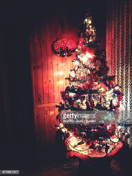 Illuminated Christmas Tree Against Wall At Home