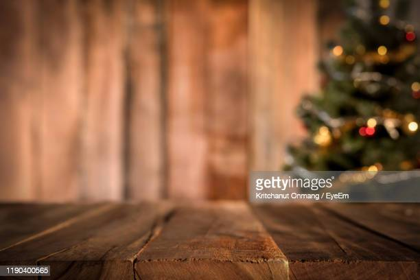 illuminated christmas tree by wooden table - premier plan net photos et images de collection