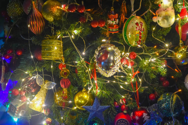 Illuminated Christmas tree , colourful Christmas ornaments with reflections on the shiny glass ornaments