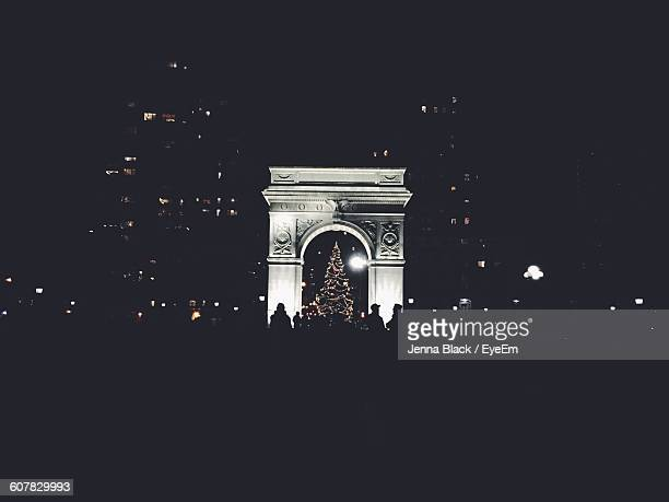 illuminated christmas tree under triumphal arch at night - washington square park stock pictures, royalty-free photos & images