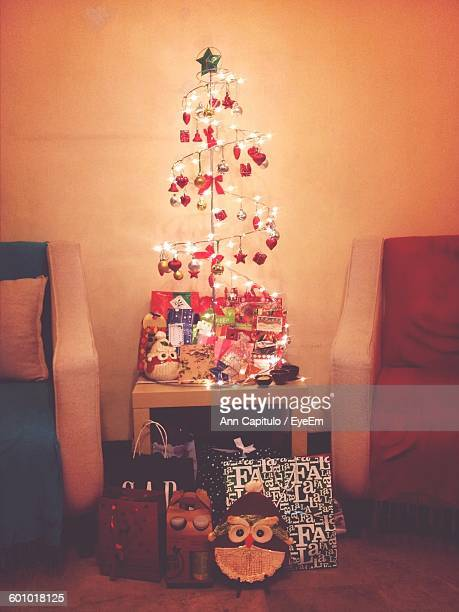 Illuminated Christmas Tree With Presents In Living Room Against Wall