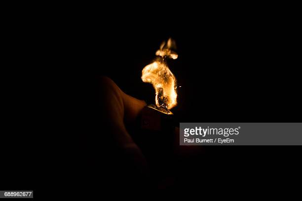illuminated cigarette lighter against black background - cigarette lighter stock pictures, royalty-free photos & images