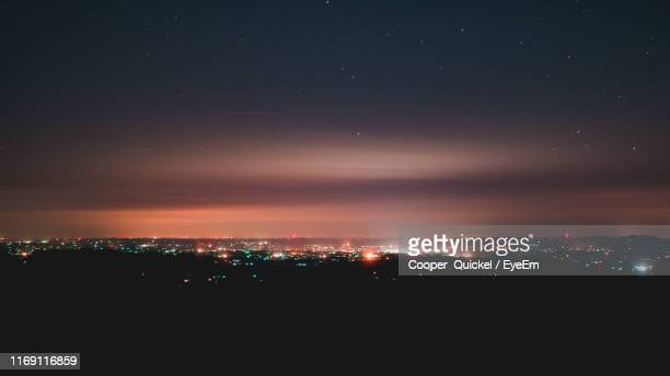 illuminated city against sky at night - winston salem stock pictures, royalty-free photos & images