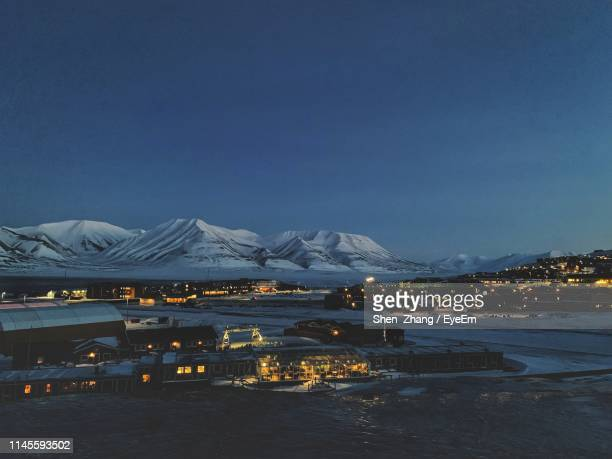 illuminated city and snowcapped mountains against clear sky at night - スヴァールバル諸島 ストックフォトと画像