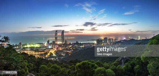 illuminated city at dusk, xiamen, fujian, china - xiamen fotografías e imágenes de stock