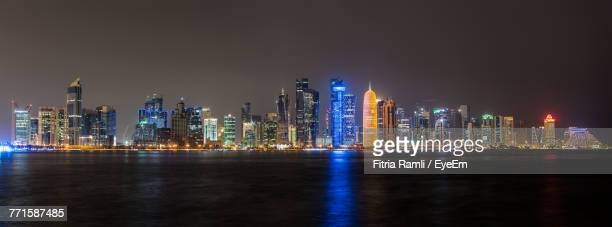illuminated city at night - doha stock photos and pictures
