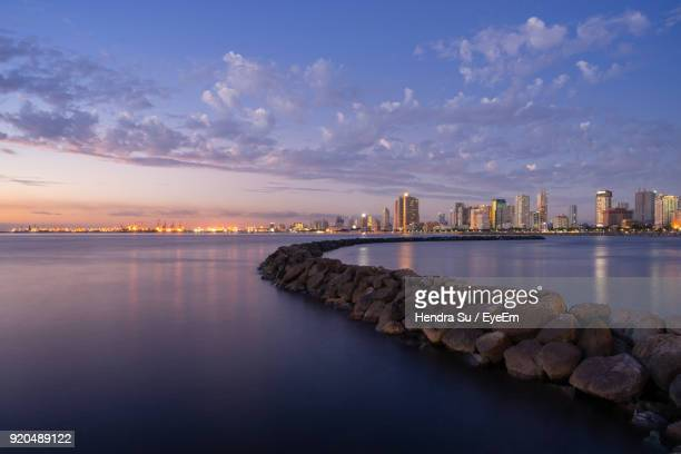 illuminated city at waterfront against sky - manila bay stock photos and pictures