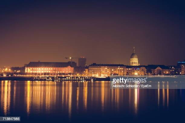 illuminated city at waterfront - albrecht schlotter stock photos and pictures