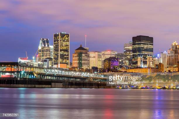 illuminated city at waterfront - montréal stock pictures, royalty-free photos & images
