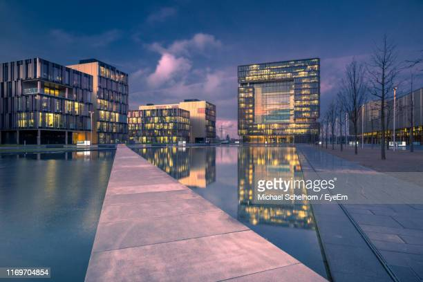 illuminated city buildings against sky at dusk - essen germany stock pictures, royalty-free photos & images