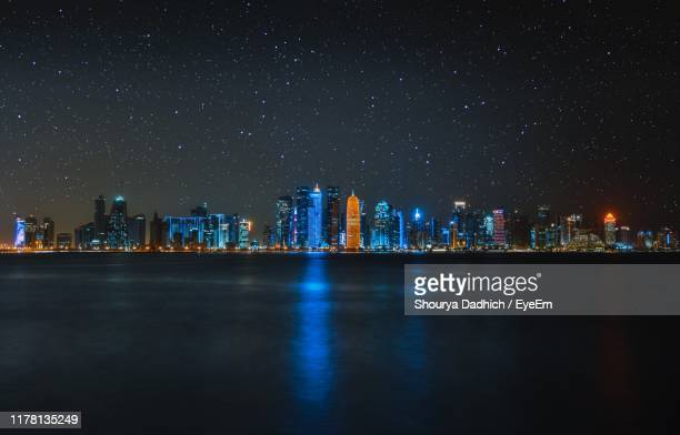 illuminated city buildings against sky at night - doha photos et images de collection