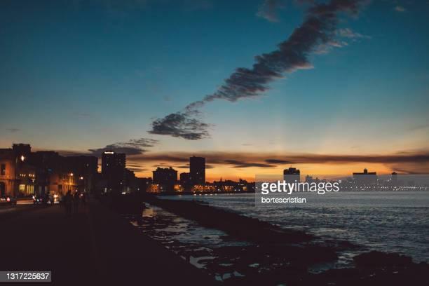 illuminated city buildings against sky during sunset - bortes stock-fotos und bilder