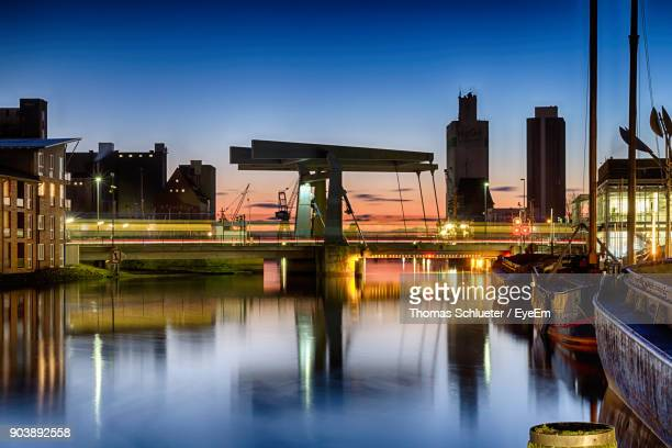 illuminated city by boats moored on river against sky at night - husum stock-fotos und bilder