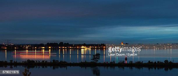 Illuminated City By Calm Lake During Dusk