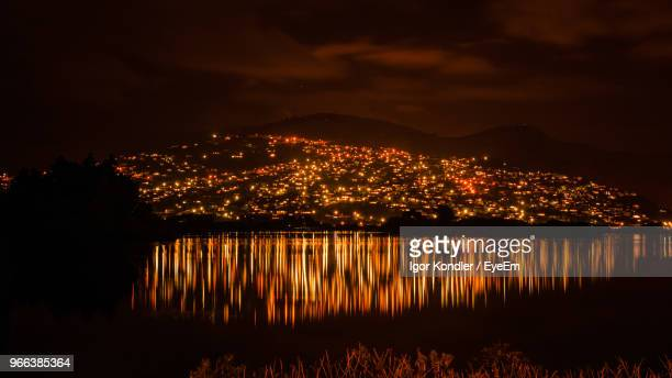 illuminated city by lake against sky at night - christchurch new zealand stock pictures, royalty-free photos & images