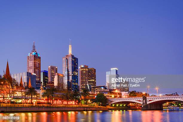 Illuminated City By Princes Bridge Over Yarra River Against Clear Sky