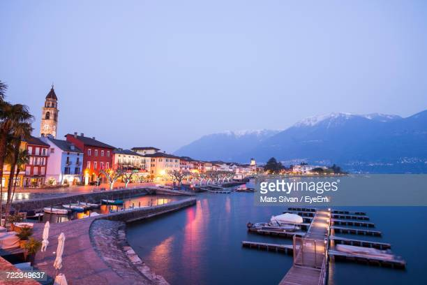 illuminated city by river against clear sky at dusk - ascona stock photos and pictures
