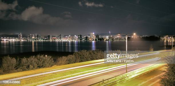 illuminated city by river against sky at night - jyväskylä stock pictures, royalty-free photos & images