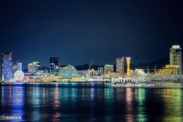 illuminated city by river against sky at night - 神戸市 ストックフォトと画像