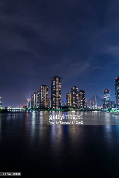 illuminated city by river against sky at night - 永代橋 ストックフォトと画像