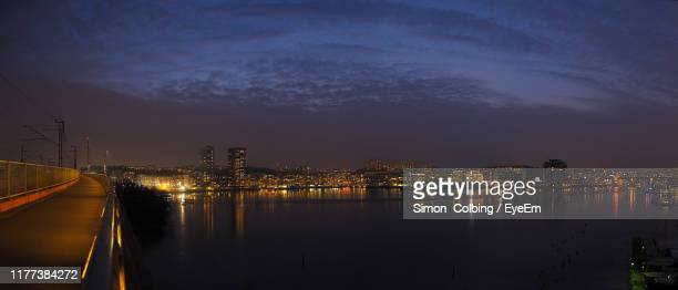 illuminated city by river against sky at night - colbing stock pictures, royalty-free photos & images