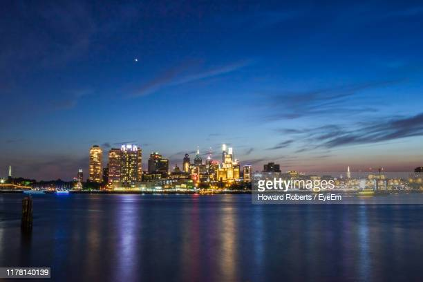 illuminated city by river against sky at night - philadelphia skyline stock pictures, royalty-free photos & images