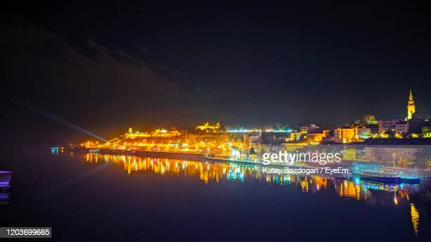 illuminated city by river against sky at night - belgrade serbia stock pictures, royalty-free photos & images