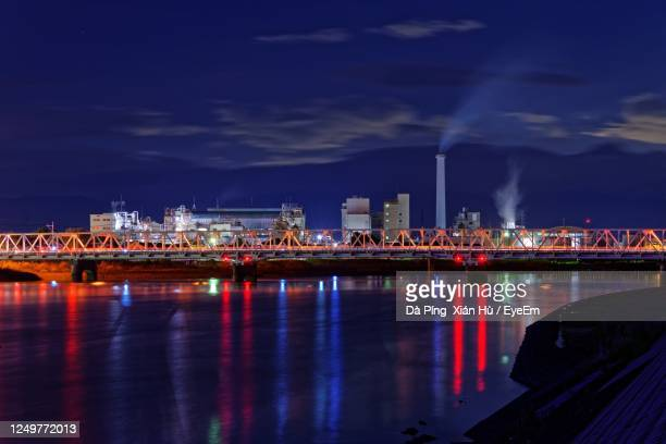 illuminated city by river against sky at night - 佐賀県 ストックフォトと画像