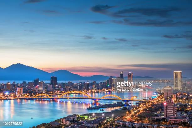illuminated city by river against sky during sunset - vietnam stockfoto's en -beelden