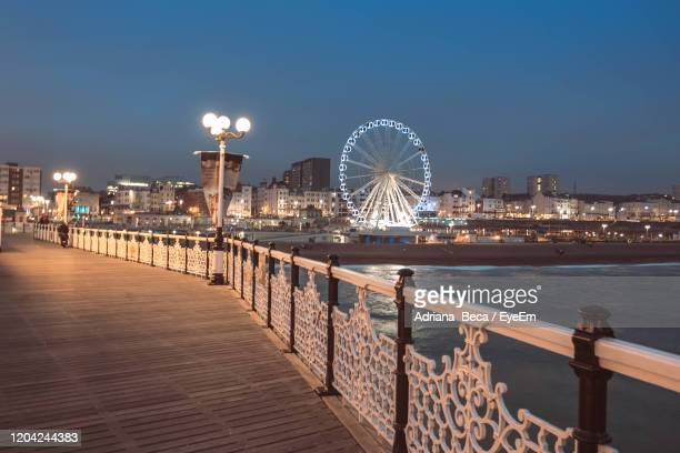 illuminated city by sea against clear sky at night - brighton stock pictures, royalty-free photos & images
