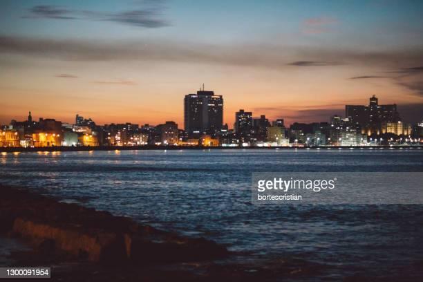illuminated city by sea against sky at dusk - bortes stock-fotos und bilder