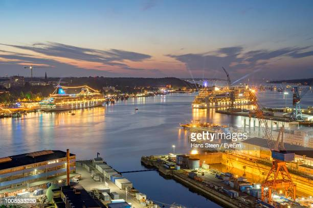 illuminated city by sea against sky at night - schleswig holstein stock photos and pictures