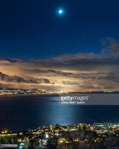 illuminated city by sea against sky at night - kanton waadt stock-fotos und bilder